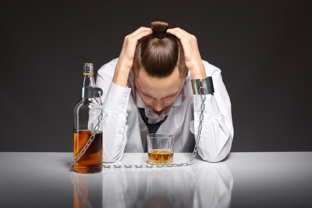 homem alcoolatra olhando para seu copo de whisjy. Alcoolismo e a relação trabalhista